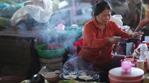 Outside Nha Trang, Vietnam - May 8 2015: Local life of ordinary people in poor traditional city of Indochina. Woman prepares food, noodles for customers. Work and business in roadside bazaar. Outdoors