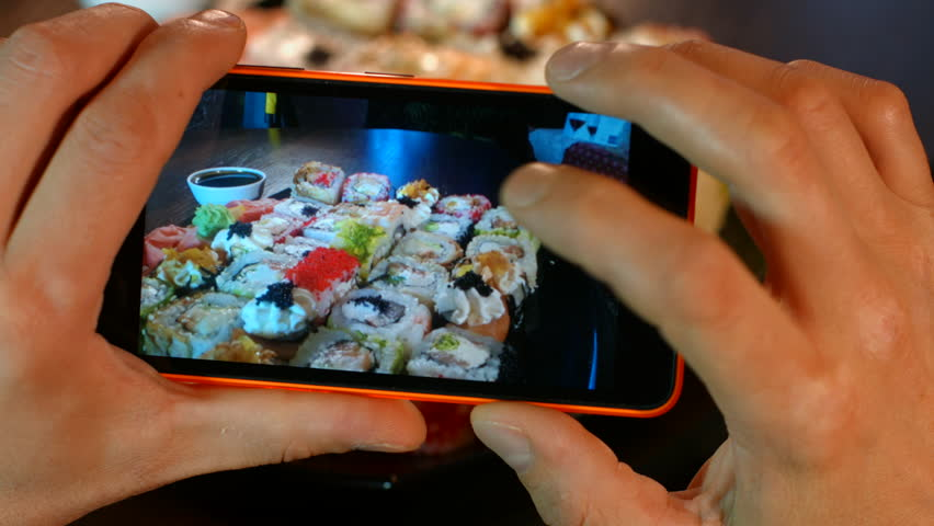 The man on the smartphone photography food seafood cooking sushi Asian cuisine. 4K 30fps ProRes (HQ) | Shutterstock HD Video #16293304