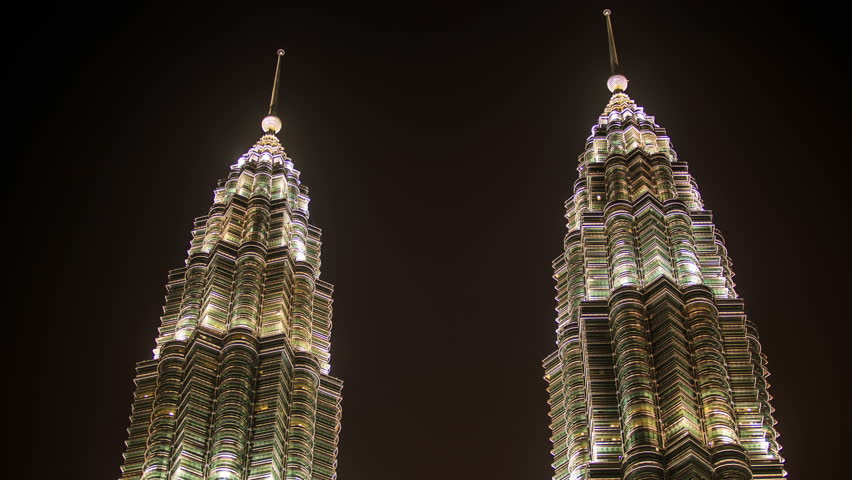 closeup night clouds motion in blue sky over Petronas Twin Towers taken from downwards