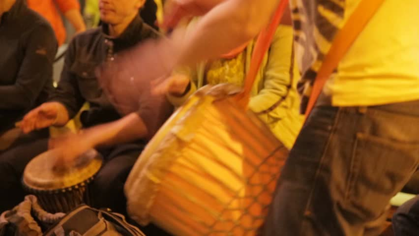 people are playing on drums and dance on the street