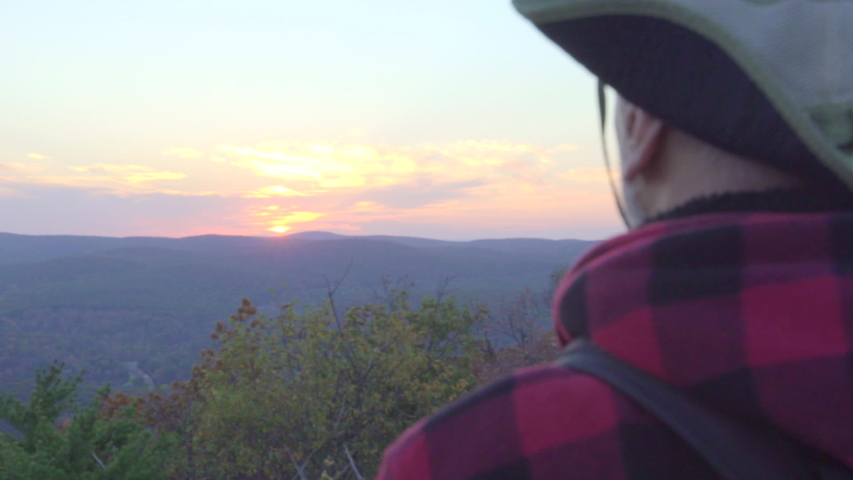 An older man admiring the sunset view while on a scenic hike in the mountains. - Model Released - Clip is HD 1920 x 1080 #16343884
