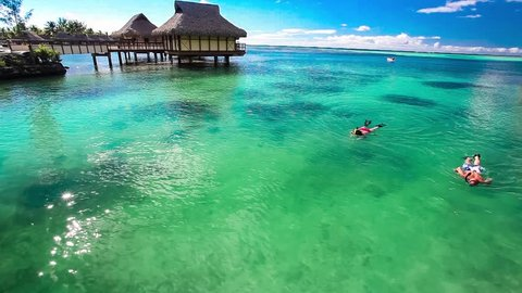 Young couple snorkeling in water next to tropical resort