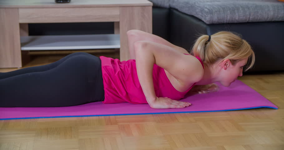 This young woman has been working out at home in her living room and now, she is doing some stretching for her stomach muscles. Close-up shot. | Shutterstock HD Video #16364224