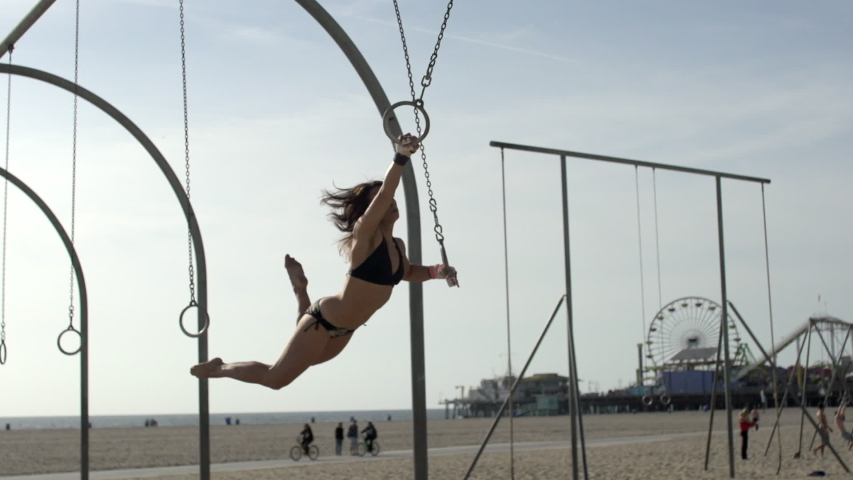 A woman in a black bikini swinging on the traveling rings at Santa Monica beach. - Slow Motion - Model Released - filmed at 59.94 fps - Clip is HD 1920 x 1080