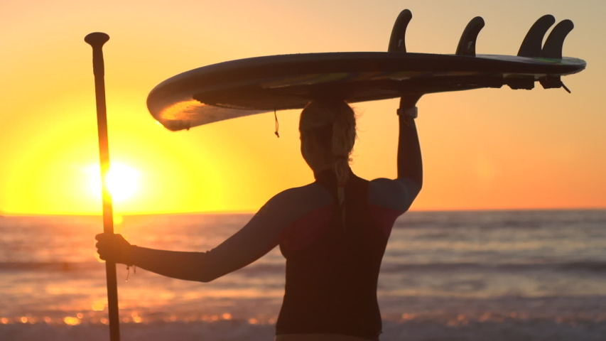 A silhouetted portrait of woman sup stand-up paddleboard surfing at the beach at sunset. - Slow Motion - Model Released - filmed at 59.94 fps - Clip is HD 1920 x 1080