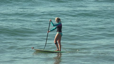 A woman sup stand-up paddleboard surfing at the beach. - Slow Motion - Model Released - filmed at 59.94 fps - Clip is HD 1920 x 1080