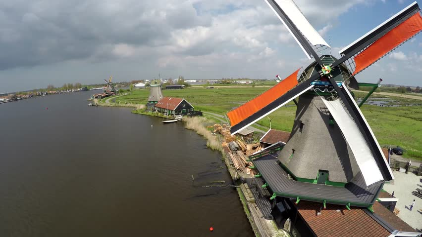 Aerial Zaanse Schans moving past windmills then turning towards mills blades turning by wind sustainable clean energy great tourist attraction Netherlands near Amsterdam drone footage bird-eye view 4k