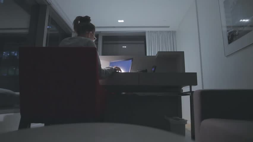 Young concentrated woman,  sitting in her room or office with french windows in the dark at the lamp.Studies late at night.Staying up late. Overworking.  Working late on laptop. | Shutterstock HD Video #16414864