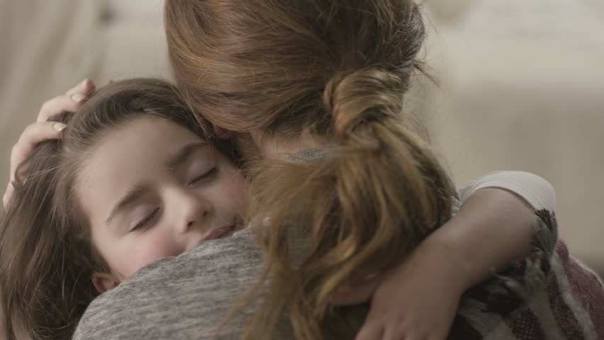 Daughter rushes into mother's arms at home and gives her a big hug. Shot on RED EPIC Cinema Camera in slow motion.