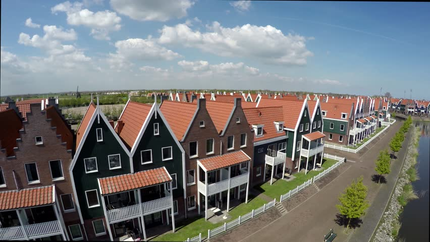 Aerial flying near the typical Dutch houses of Volendam then gaining height showing the harbor town is popular tourist attraction in Netherlands known for old fishing boats and traditional clothing 4k