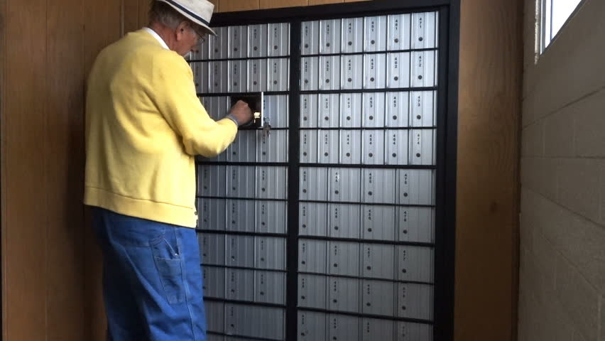 FOUNTAIN GREEN, UTAH - APRIL 2016: Older senior citizen man in yellow sweater, coveralls and fisherman hat with grey goatee getting mail from rural America Post Office Box.