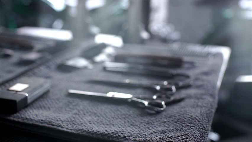Closeup of tools, scissors, comb and razor in barber shop or men's beauty parlor. Dolly shot