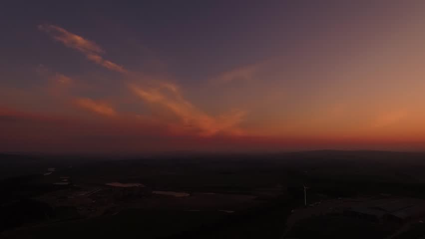 Aerial pan of orange sunset with orange and pink clouds over small town
