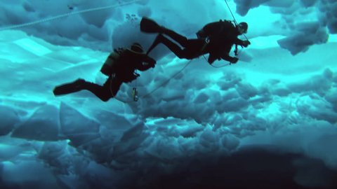 Unique extreme underwater shooting scuba dive beneath ice at geographic  North Pole in cold waters. Fantastic views of the lump of ice in water. ICE CAMP BARNEO, NORTH POLE, ARCTIC - APRIL 10, 2015