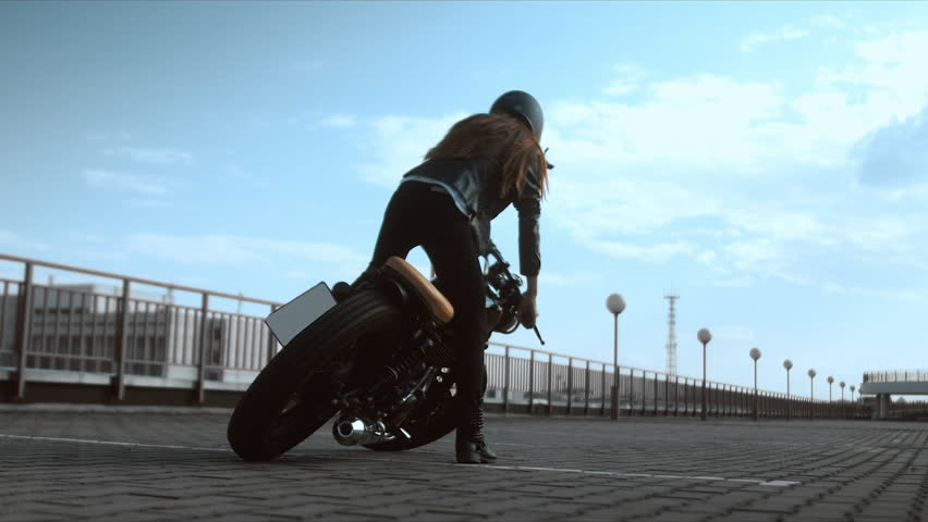 Young sexy Caucasian female sits on a motorcycle, than falling on the ground, novice biker fail. 60 FPS slow motion. Blackmagic URSA Min