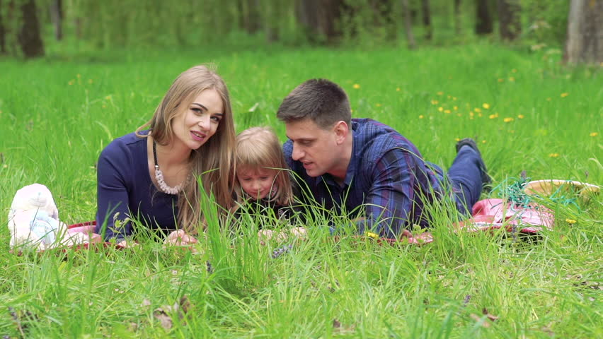 Family with baby girl resting on a grass in a park. Slowly | Shutterstock HD Video #16519474