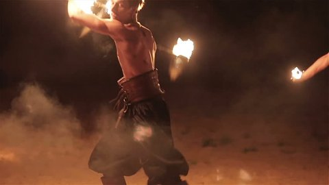 Fire show performance. Three handsome male fire performers dance twirling two fire batons staff ignited from both sides each. Slow motion