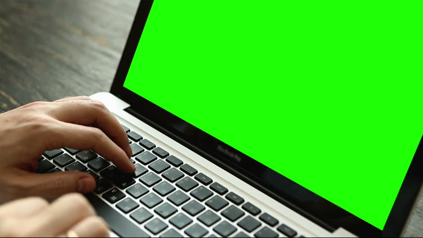 Hand of a man working at laptop computer typing on a keyboard on dark desktop. Close up view with green screen | Shutterstock HD Video #16546051