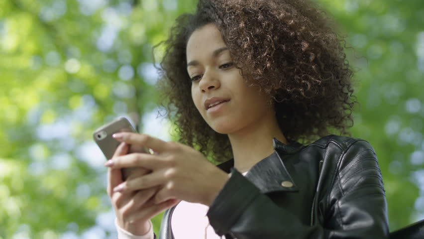 Portrait of relaxed young lady in a summer park reading a text message on her mobile phone. Beautiful young girl with dark curly hair using her cell phone, outdoor.
