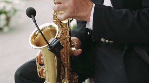 Close-Up on Fingers Pressing the Keys of the Instrument. Musician Playing the Saxophone in the Street. the Camera Moves Up. in Fixed Wireless Microphone Saxophone. a Man in a Black Suit and White