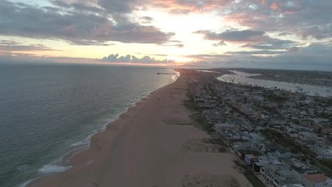 Newport Beach, California Peninsula aerial footage at sunset. Beach most deserted. Views to the East of the Newport Beach Harbor and Balboa Island