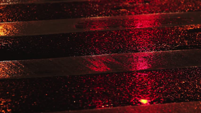 Rainy night in the city. Reflection of traffic lights changing from red to green