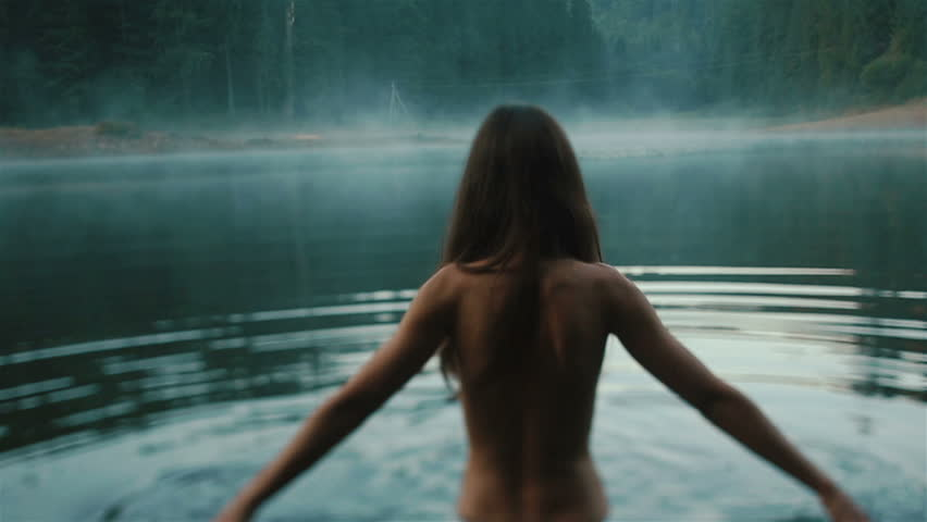 Beautiful naked fairy or mermaid with long dark hair in the mystical foggy mountain lake on back view. Fantasy magic world in mountains | Shutterstock HD Video #16656865