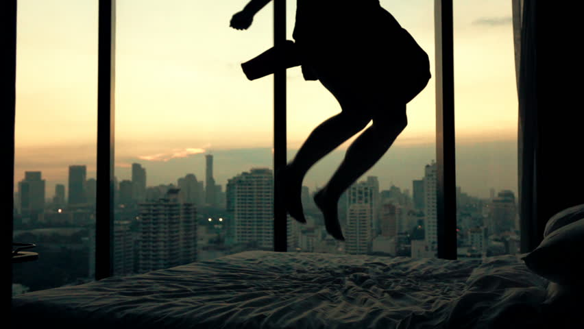 Happy woman jumping on bed in luxury apartment, super slow motion, 240fps    Shutterstock HD Video #16666303