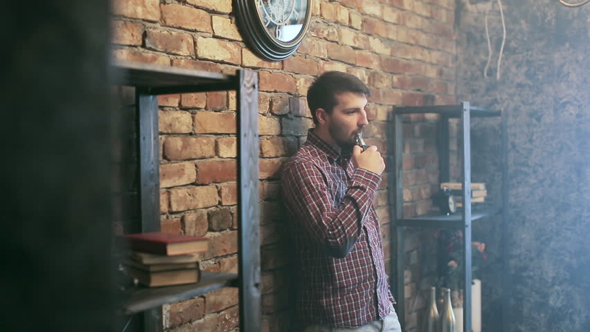 young stylish man with electronic cigarette vaping