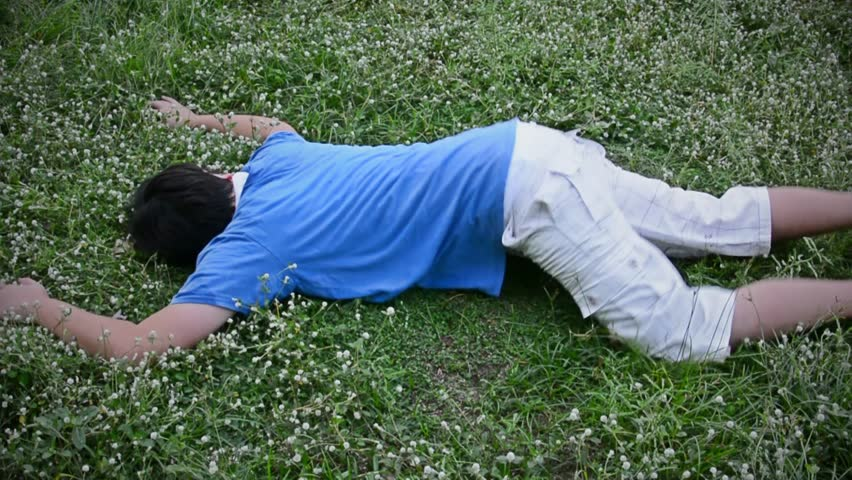 An Asian Thai man drop dead on the grassy ground field and twitching in HD