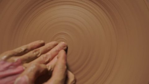 Hands working on a potter's wheel , making a relief on a clay plate