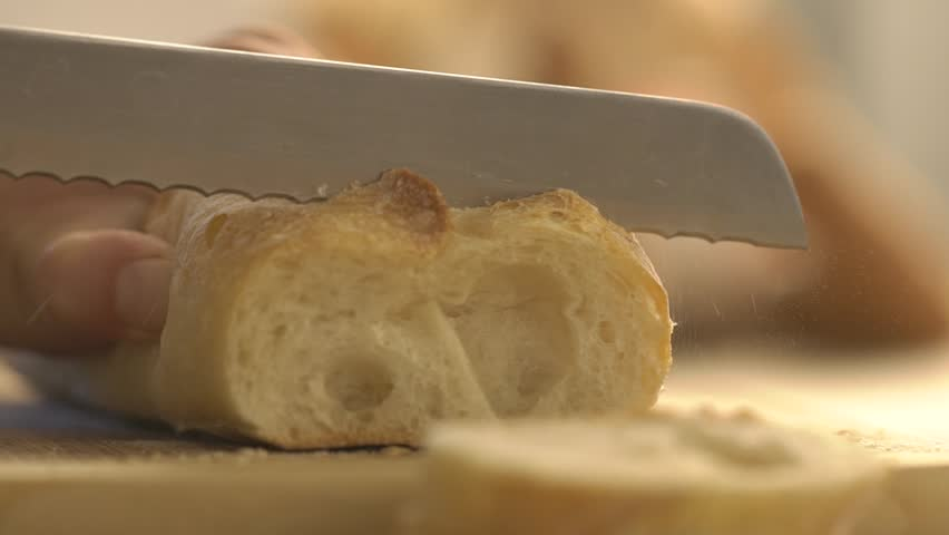 Slicing baguette on table. Baguette traditional French bread on the table cutting close-up. Fresh French traditional bread baguette on chopping board cutting with knife