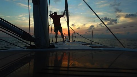 Young man standing with his back on the bow sailing yacht and looks forward in the course of the boat. Beautiful sunset sky in background. Look into the distance. Standing at deck of boat.