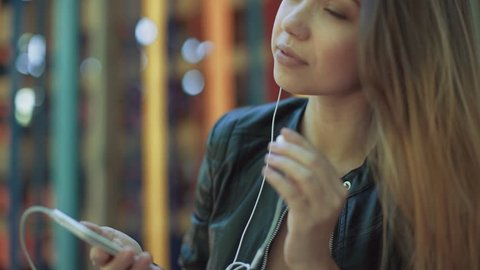 Girl listening music from smart phone mp3 player