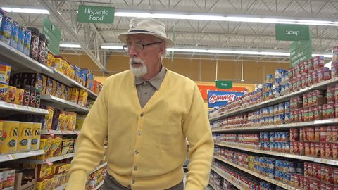 FOUNTAIN GREEN, UTAH - April 2016: Lonely old male senior citizen from the baby boomer generation pushes a shopping cart through the isles of a local grocery store while shopping for groceries.