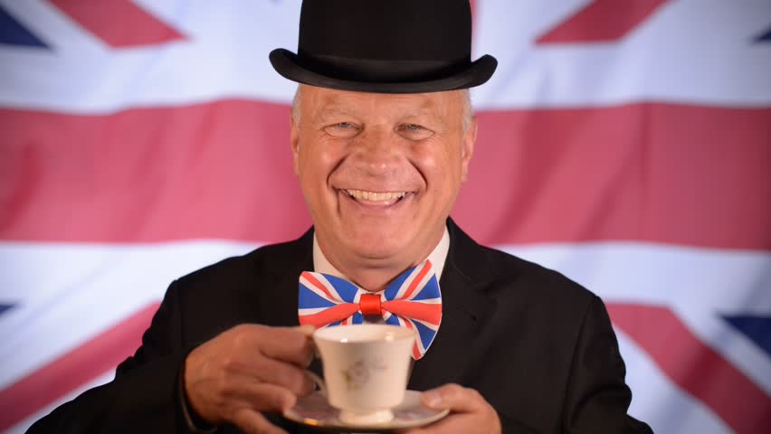 Laughing British businessman, takes a sip of tea from the cup, whilst the Union Jack flag blows in the background.
