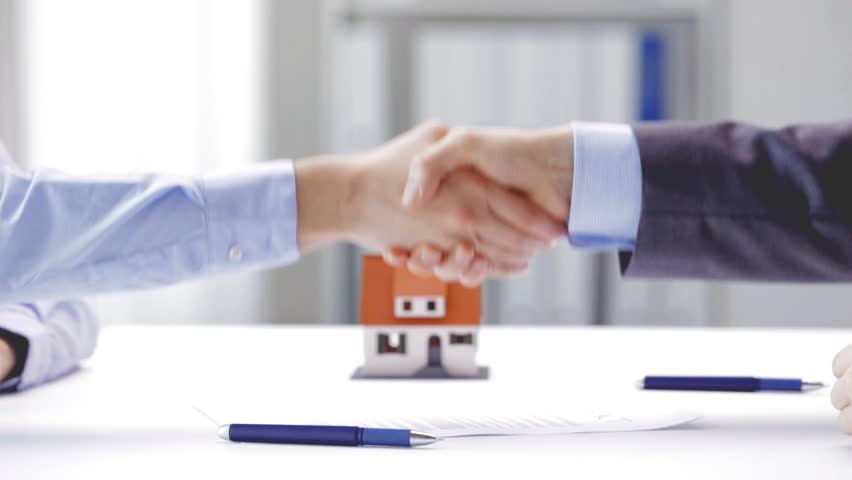 Business, real estate, deal and people concept - man giving house keys to woman and shaking hands at office