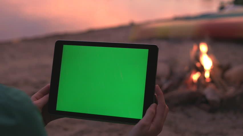 Tablet with Green Screen on Beach during a Sunset and Campfire.