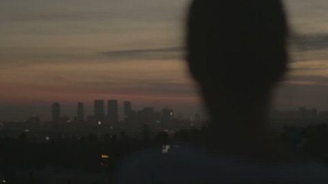 Girl looks out at LA skyline at sunset. Los Angeles, CA - USA: March, 2016