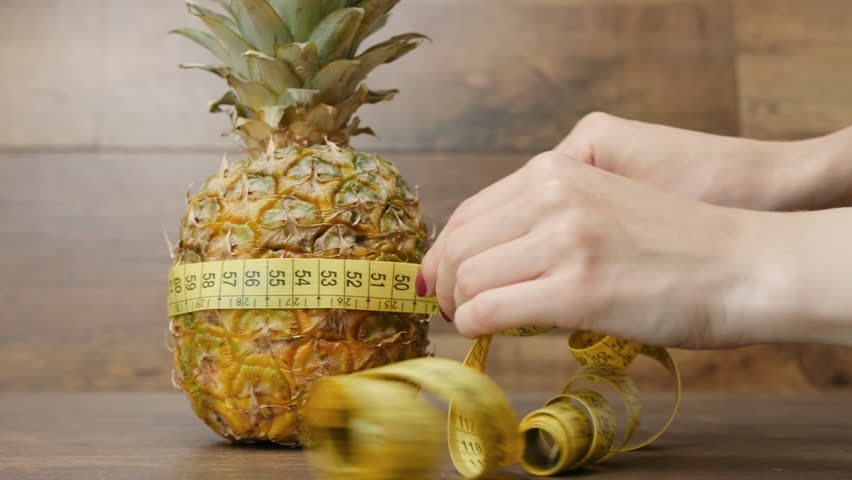 Diet weight loss fitness health care concept with measure tape and pineapple. Woman hand measures pineapple with measurement tape, metric ribbon on wooden background. Diet heathy lifestyle.