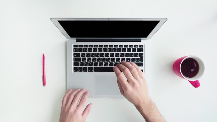 Top view of white desk with office supplies. Man using his laptop computer, typing, surfing and drinking coffee | Shutterstock HD Video #16858324