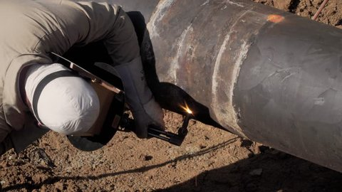 Pipeline welder uses a torch to cut s section from a oil pipeline that is being repaired.