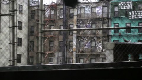 NEW YORK - MAY 4, 2016: gritty tenements buildings covered in graffiti view from moving B Train - subway in NYC. MTA serves the 5 boroughs of the city.