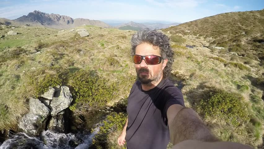 Adult male caucasian hiker with beard and sunglasses taking selfie on the mountain summit. Alps landscape in the background and little stream flowing. Natural tones, wide angle view, slow motion. #16869154