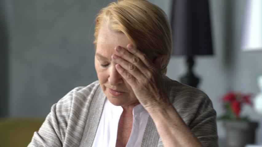 elderly woman with headache takes a pill