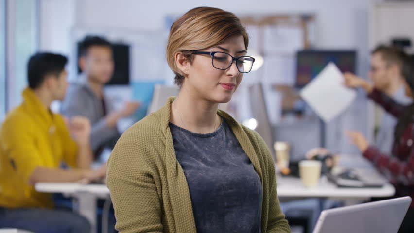 4K Portrait of smiling casual businesswoman working on laptop in office with colleagues in background. Shot on RED Epic. UK - April, 2016 | Shutterstock HD Video #16903414
