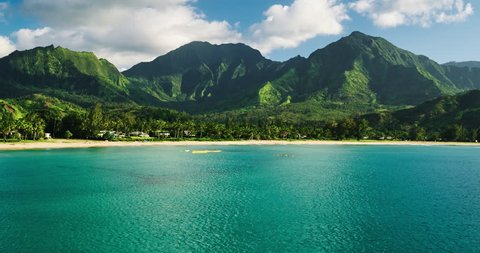 Aerial view flying over hawaiian canoes towards beautiful green mountains and white sandy beach. Hanalei Bay, Kauai