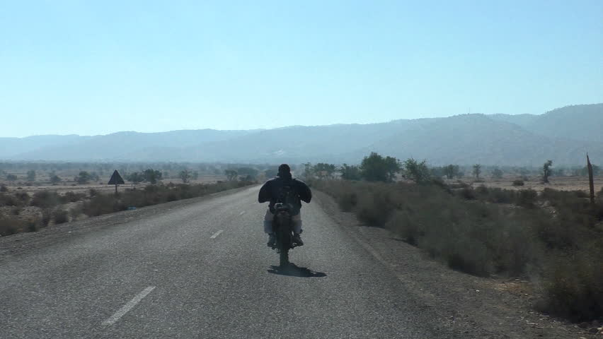 View from moving car of backside of local man riding motorcycle on rural asphalt road in semi desert landscape of Morocco, Africa.