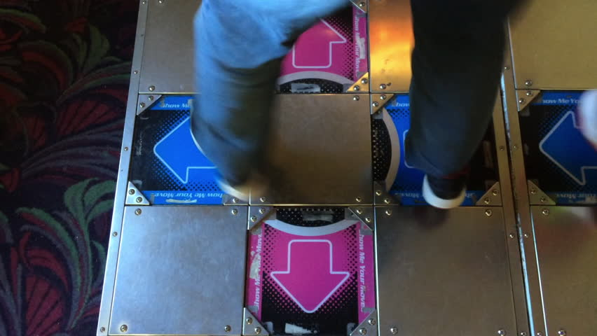 USA - CIRCA 2016: Person playing rhythm dancing game, called Dance Dance Revolution, in arcade.  This game is a great source of exercise for someone interested in video games and health.