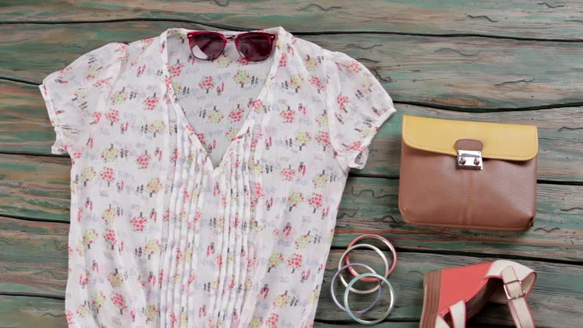White blouse and wedge sandals. Bicolor brown purse and bracelets. Clothing on green wooden shelf. Girl's outfit with stylish footwear. | Shutterstock HD Video #16945294